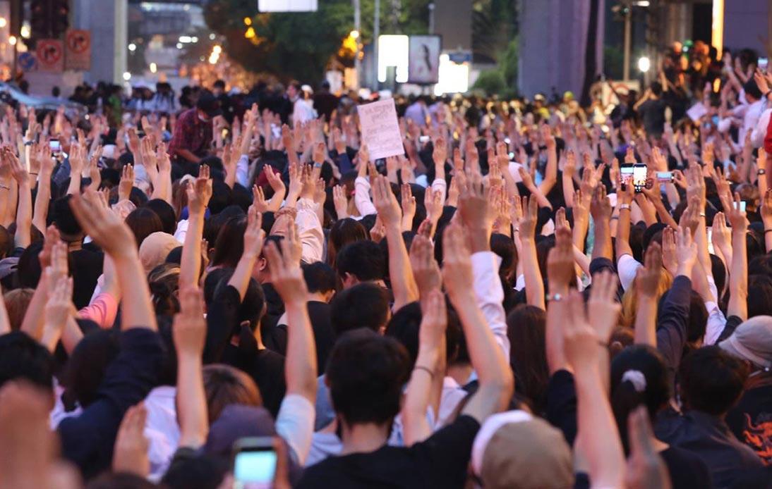 Thai protesters with their hand sign